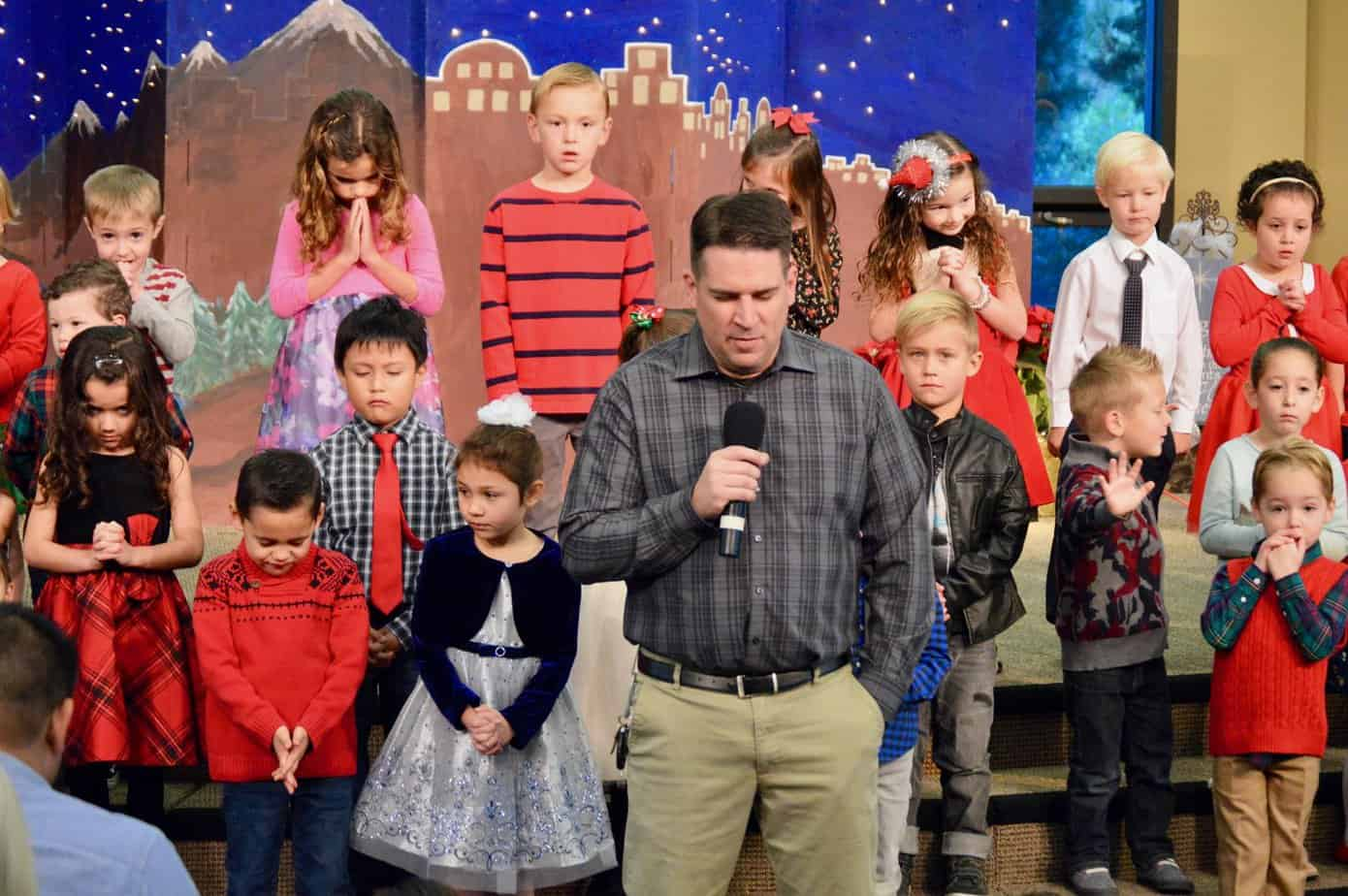 Youth Minister Aaron Stevens pray at The Christmas Children Show - Mission Viejo Church of Christ